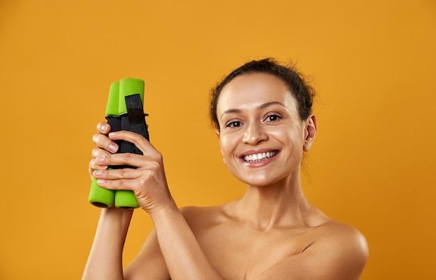 Mulher bonita sorrindo e segurando halteres nas mãos, isoladas em backgroung amarelo