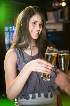 Mulher bonita sorrindo enquanto brindando seu copo de cerveja em bar