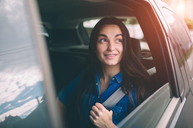 Mulher bonita sorrindo enquanto está sentado no banco de trás do carro