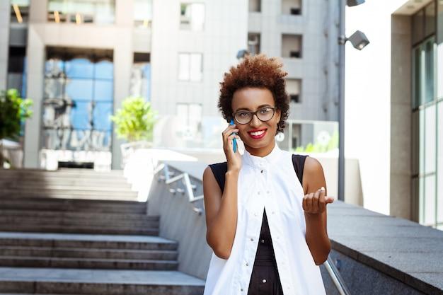 Mulher bonita sorrindo, falando no telefone, andando pela cidade