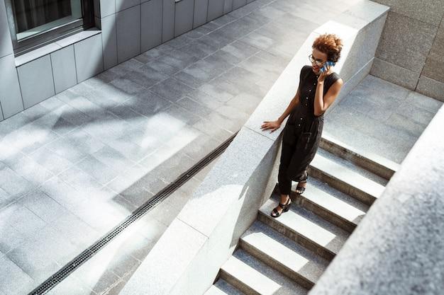 Mulher bonita sorrindo falando no telefone descendo escadas