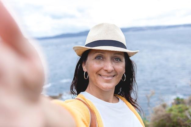 Mulher bonita sorrindo feliz ao ar livre em um belo dia, usando um chapéu de verão, tirando uma foto de selfie