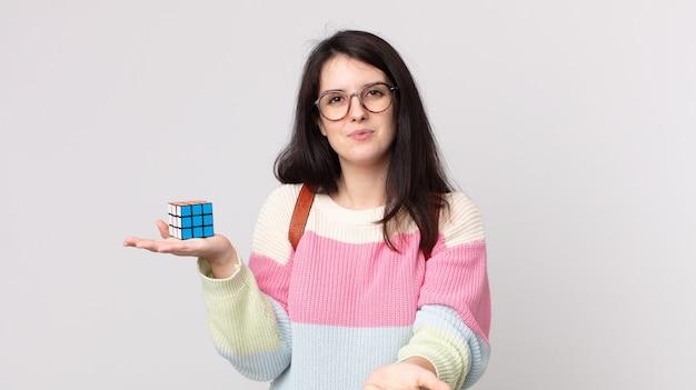 Mulher bonita sorrindo feliz com simpatia e oferecendo e mostrando um conceito e resolvendo um jogo de inteligência