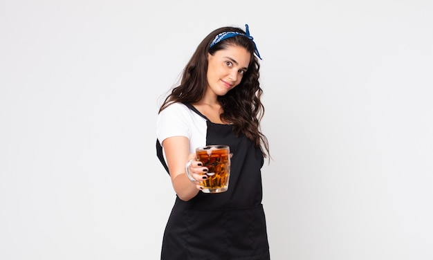 Mulher bonita sorrindo feliz com simpatia e oferecendo e mostrando um conceito e segurando um copo de cerveja