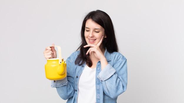 Mulher bonita sorrindo feliz e sonhando acordada ou duvidando e segurando um bule de chá