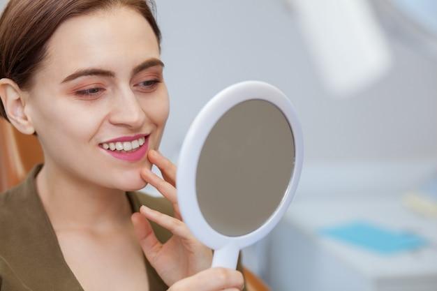 Mulher bonita sorrindo, olhando no espelho na clínica odontológica
