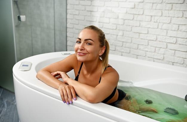Mulher bonita sorrindo para a câmera enquanto desfruta de hidromassagem e tratamentos de beleza em uma cápsula de spa moderna no centro de spa