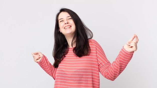 Mulher bonita sorrindo, sentindo-se despreocupada, relaxada e feliz, dançando e ouvindo música, se divertindo em uma festa