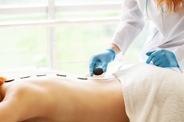 Mulher bonita spa massagem com pedras quentes tratamentos de beleza.