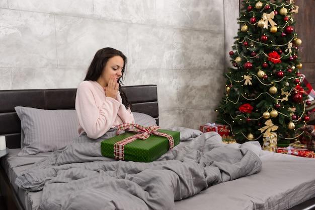 Mulher bonita surpresa acordar e se alegrar com seu presente de natal enquanto está sentada em uma cama no quarto em estilo loft com árvore de natal com muitos presentes
