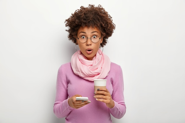 Mulher bonita surpresa com cabelo crespo verifica o feed de notícias, recebe mensagem de choque, segura café para viagem, não consegue acreditar em algo, usa óculos ópticos e suéter roxo, posa em ambientes fechados
