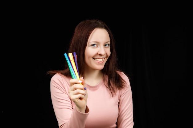 Mulher bonita tem marcadores ou canetas na mão e mostra em um fundo preto. copie o espaço para o texto.