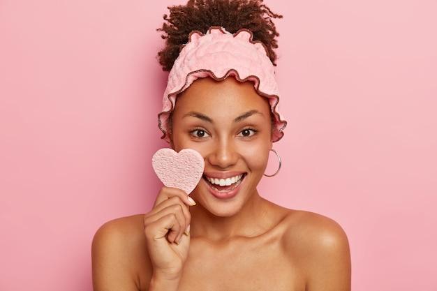 Mulher bonita tem pele saudável, limpa o rosto com esponja cosmética, sorri positivamente, mostra os dentes brancos, usa bandana de chuveiro, toma banho após o trabalho, isolada na parede rosa