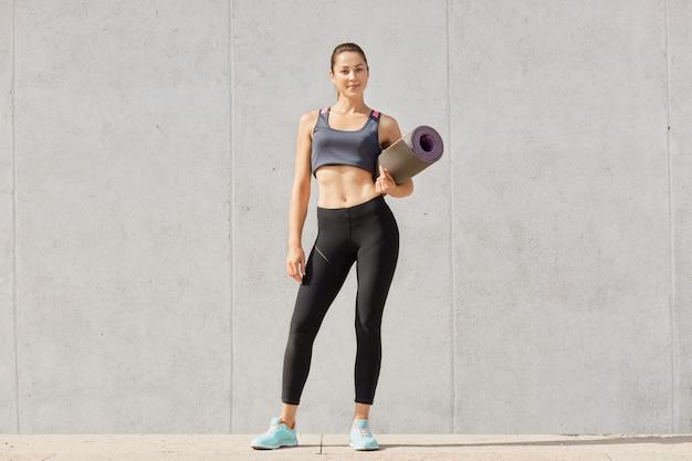 Mulher bonita tem treino, vestido com roupas esportivas