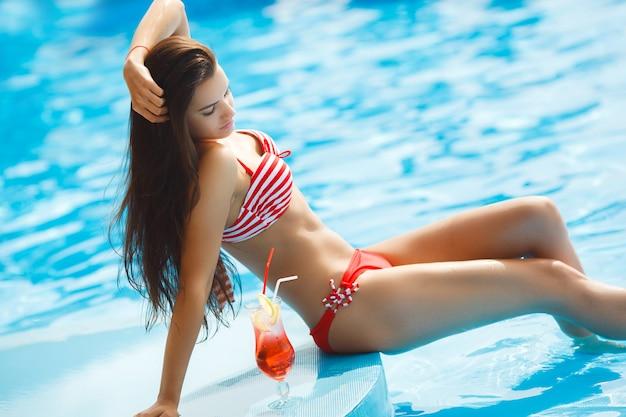 Mulher bonita, tendo um bronzeado natural perto da piscina.