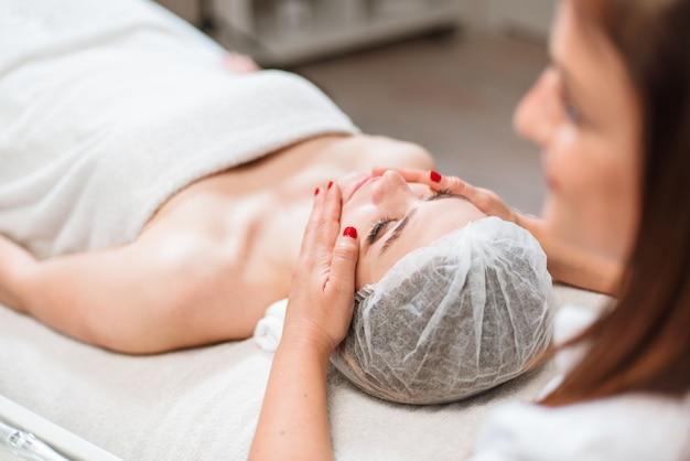 Mulher bonita, tendo um tratamento de beleza de massagem facial