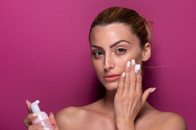 Mulher bonita, tentando o produto de cuidados da pele