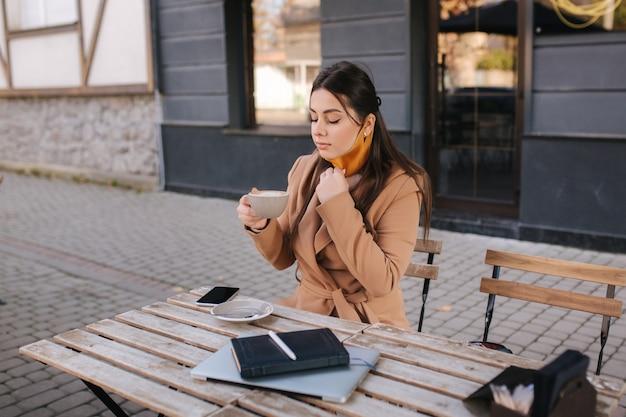 Mulher bonita tira a máscara protetora para beber café. mulher sentada ao ar livre no terraço e bebe café.