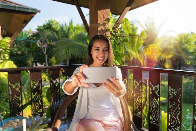 Mulher bonita tirando foto de selfi na célula telefone inteligente na manhã