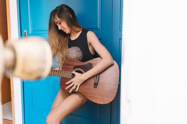 Mulher bonita tocando violão no corredor