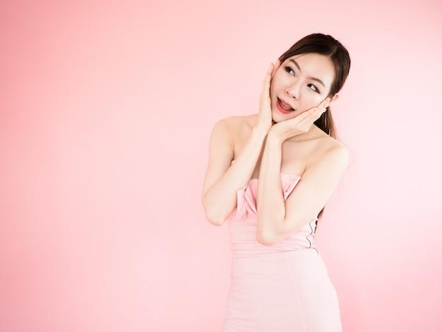 Mulher bonita, tocar, dela, bochecha, com, dedos, menina asiática, desgaste, vestido strapless