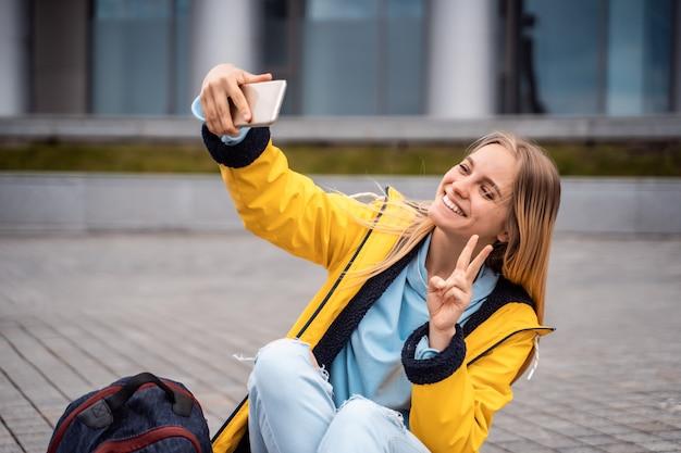 Mulher bonita toma selfie no smartphone e senta-se no skate