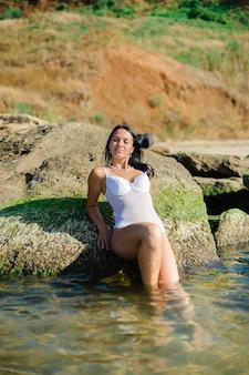 Mulher bonita tomando banho de sol na costa do oceano.