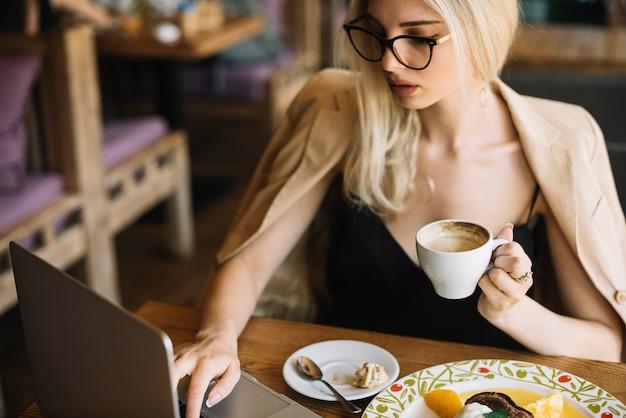 Mulher bonita tomando café no café enquanto estiver usando o laptop
