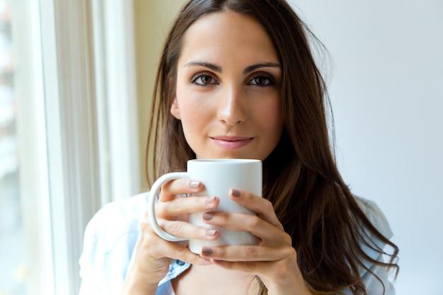 Mulher bonita tomando cafe pela manhã perto da janela.
