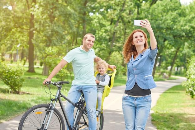 Mulher bonita tomando selfie com marido e bebê de bicicleta enquanto relaxa ao ar livre no parque.
