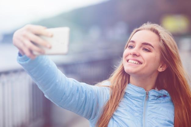Mulher bonita tomando uma selfie. linda garota andando nas ruas e fotografando alguns pontos turísticos. loira tirou fotos de si mesma, instagram