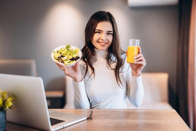 Mulher bonita trabalhando com seu laptop enquanto segura um copo de suco de laranja e salada na cozinha. trabalhar em casa em regime de quarentena. distanciamento social auto-isolamento.