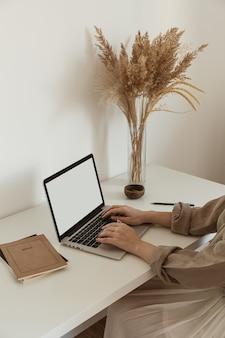Mulher bonita trabalhando, digitando no laptop. design de interiores de espaço de trabalho de escritório em casa confortável e aconchegante