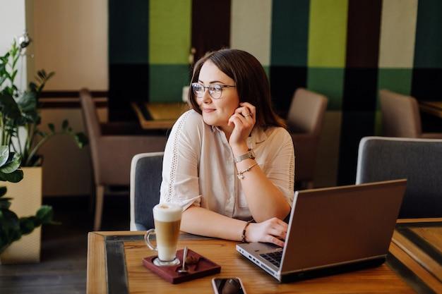 Mulher bonita trabalhando em seu laptop e telefone em um elegante restaurante urbano