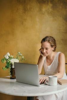 Mulher bonita trabalhando em seu laptop em um café