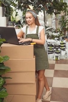 Mulher bonita trabalhando em uma estufa no laptop e fazendo anotações