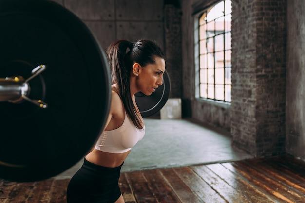 Mulher bonita treinando e fazendo exercícios funcionais na academia Foto Premium