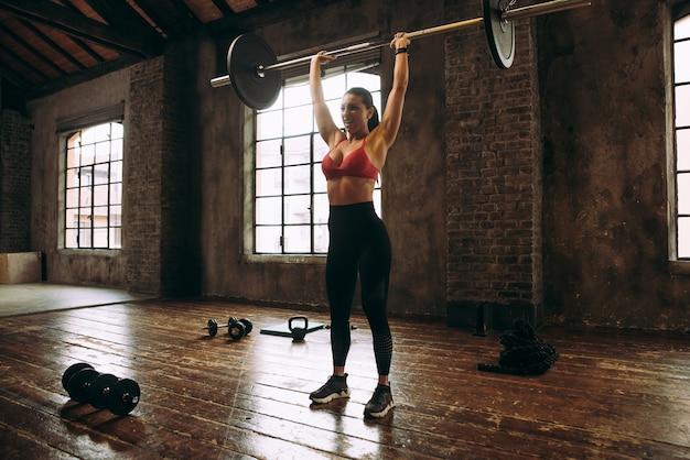 Mulher bonita treinando e fazendo exercícios funcionais na academia