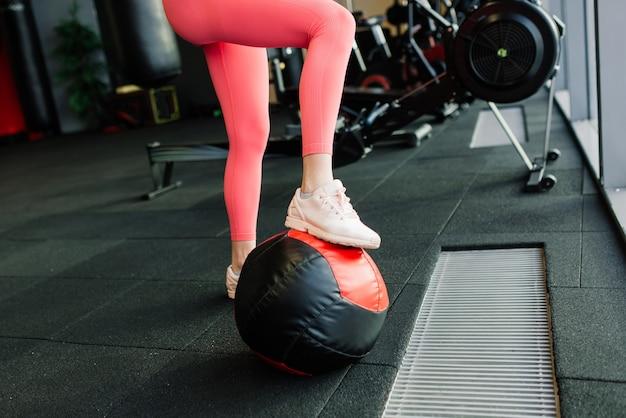Mulher bonita treinando pilates com bola na academia