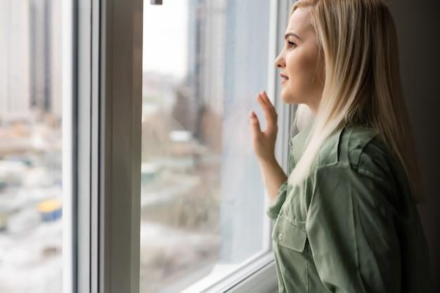 Mulher bonita triste olhando pela janela