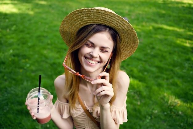 Mulher bonita, um copo com uma bebida no estilo de vida do parque