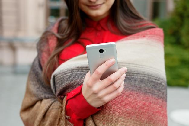 Mulher bonita usando aplicativo de tecnologia de telefone inteligente nas ruas da cidade, vivendo um estilo de vida feliz urbano. senhora de negócios digitando a mensagem em seu telefone
