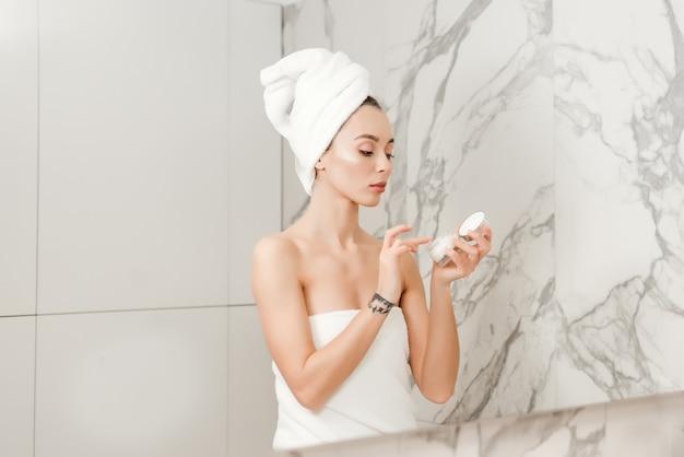 Mulher bonita usando cosméticos creme no banheiro após o banho embrulhado na toalha