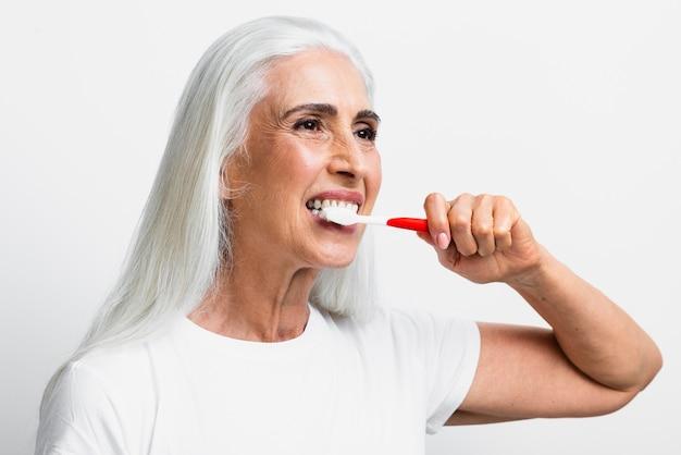 Mulher bonita usando escova de dentes