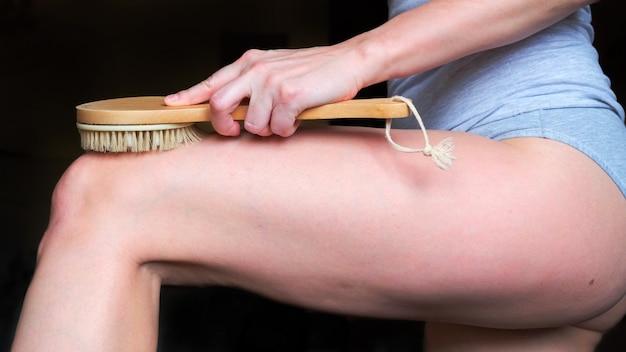 Mulher bonita usando escova no quadril, closeup, cuidados com o corpo