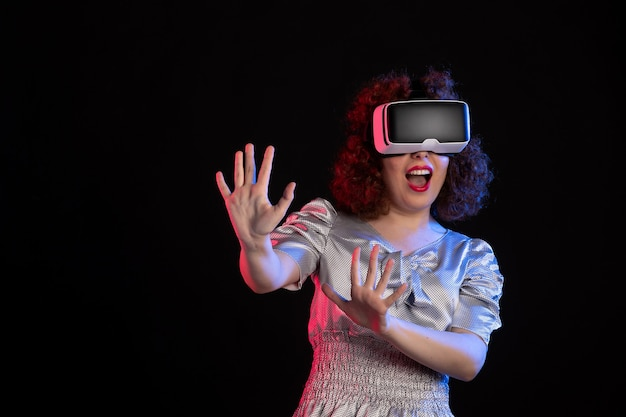 Mulher bonita usando fone de ouvido de realidade virtual na superfície escura