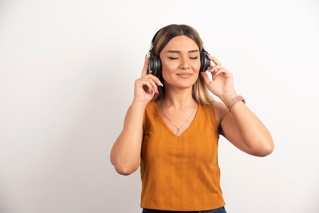 Mulher bonita usando fones de ouvido em fundo branco.