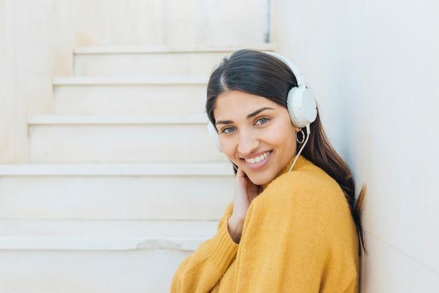 Mulher bonita usando fones de ouvido, olhando para a câmera