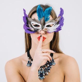 Mulher bonita usando máscara de penas com o dedo nos lábios