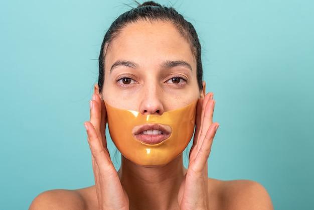 Mulher bonita usando máscara facial com gel de colágeno